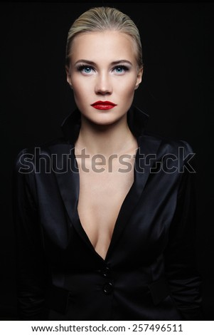Young beautiful blond glamorous woman in black silky jacket over dark background - stock photo