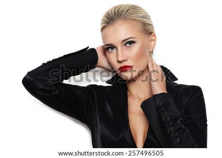 Young beautiful blond glamorous woman in black silky jacket over white wall