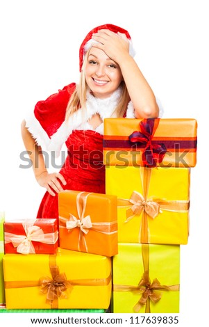 Young beautiful blond happy smiling woman in Santa costume surrounded by Christmas gift boxes, isolated on white background. - stock photo