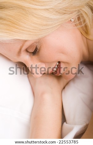 young beautiful blond sleeping woman on bed - stock photo