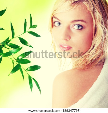 Young beautiful blond teen woman dressed in white bathrobe, against abstract green background  - stock photo