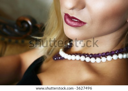 Young beautiful blond with full red lips and soft smile, sitting, white and purple beads on her neck - stock photo