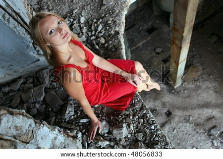 Young beautiful blond woman in a red dress sitting on the edge of the floor in abandoned construction