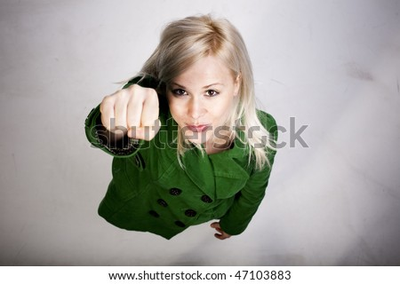 Young beautiful blond woman in a superman pose from above on dirty white floor. Girl power concept - stock photo