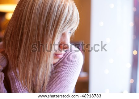 young beautiful blond woman in cafe (shallow DOF) - stock photo