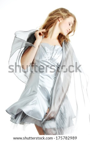 Young beautiful blond woman in elegant, evening, silver dress dancing with wind (hair blowing), isolated on white background. - stock photo