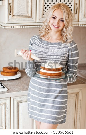 Young beautiful blond woman in winter dress making cake with cream and berries at the white vintahe kitchen. Series - stock photo