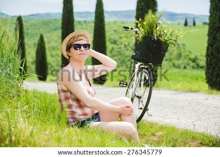 Young beautiful blond woman on vacation in Tuscany, riding a bicycle between cypresses.