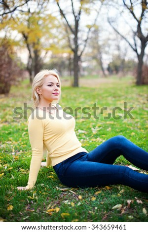 Young beautiful blond  woman sitting on grass  looking away