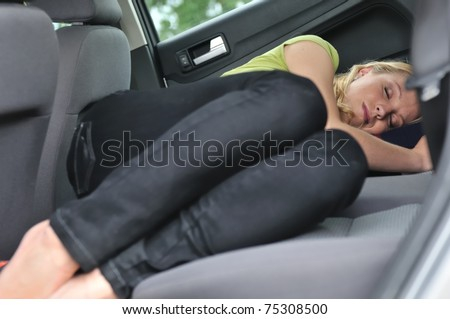 Young beautiful blond woman sleeps in car on back seat - lifestyle portrait - stock photo