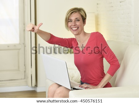 young beautiful blond woman smiling happy and cheerful working at home living room with laptop computer on sofa couch satisfied and relax in domestic technology and internet concept - stock photo