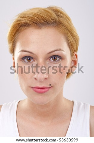 Young beautiful blond woman staring at camera - stock photo