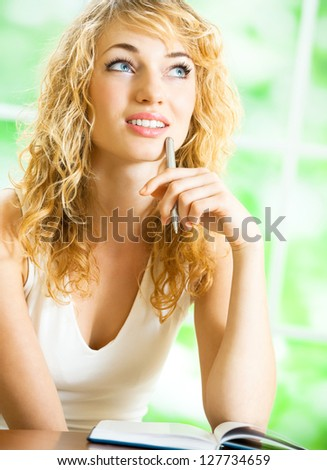Young beautiful blond woman studying with notebook or organiser, indoors - stock photo