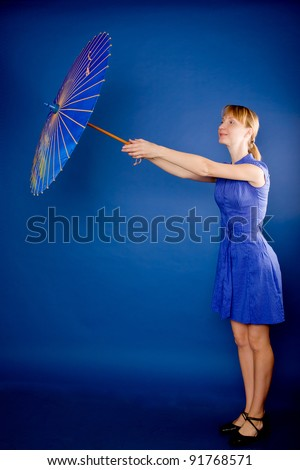 Young beautiful blond woman with a Japanese umbrella. Isolated on blue. - stock photo