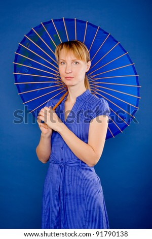 Young beautiful blond woman with a Japanese umbrella. Isolated on blue background with clipping path. - stock photo