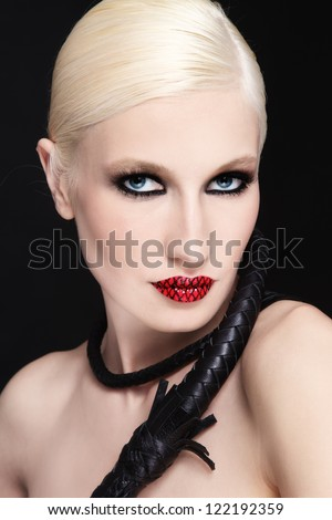 Young beautiful blond woman with braided bull whip - stock photo