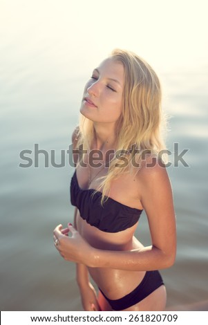 Young beautiful blond woman with eyes closed wearing black bikini relaxing in water on summer day outdoors background - stock photo