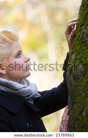 Young beautiful blonde caressing a tree - stock photo