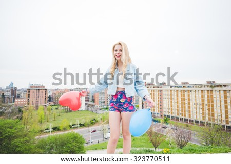 Young beautiful blonde caucasian girl playing with colorful  heart shape balloons with city in background, looking in camera smiling - childhood, carefreeness concept - stock photo