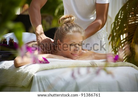 Young beautiful blonde caucasian woman gets massage and beauty treatment in luxury resort. Horizontal shape, side view - stock photo