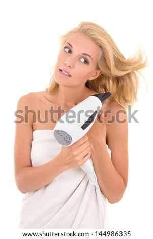 young beautiful blonde drying her hair with hairdryer - stock photo