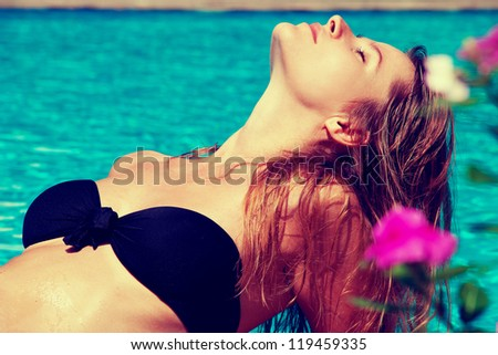 Young beautiful Blonde Female resting in the swimming pool on the sunny day. Outdoor shot, Horizontal. - stock photo