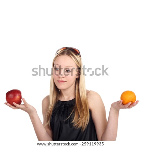 young beautiful blonde girl choicing between apple and orange - stock photo