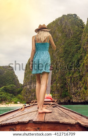 Young beautiful blonde girl cruising on retro wood boat by Andaman sea and behind her you can see Island in full glory. She's turned his back and enjoying the view. - stock photo