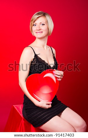 Young beautiful blonde girl hugs a big heart. Feast of St. Valentine's Day.