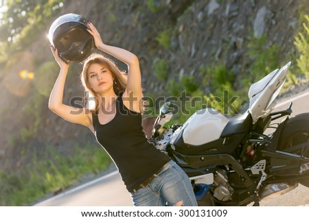 Young beautiful blonde girl in trendy jeans and a black t-shirt removes his helmet near modern motorcycle. Outdoor portrait in soft sunny colors. - stock photo