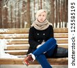 Young beautiful blonde girl sitting on the bench in winter park - stock photo