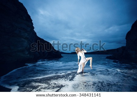 Young beautiful blonde girl wearing white dress in freezing cold water after sunset. - stock photo