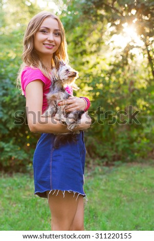 young beautiful blonde girl with little dog on her hands in park in sunny day - stock photo