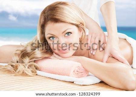 Young beautiful blonde having a professional massage on the beach background. Looking at the camera and smiling. Beautiful young woman relaxing with hand massage at spa