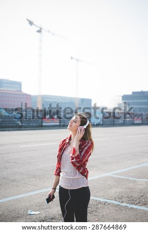 young beautiful blonde hipster woman in the city listening to music with headphones and smartphone