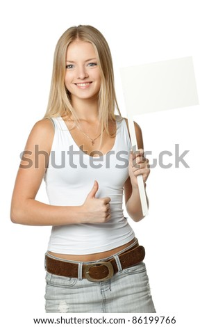 Young beautiful blonde holding blank white flag / board sign and showing thumb up sign over white background - stock photo