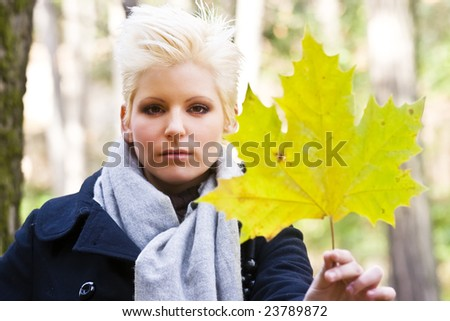 Young beautiful blonde holding golden leaf - stock photo