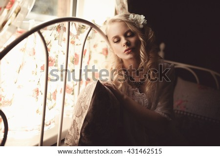 Young beautiful blonde in the bed at morning time near window under Sun rays with flower in the hair. Tender romantic mood - stock photo
