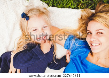 Young beautiful blonde mother and her cute little daughter smiling and relaxing in park in summer. Both wear blue dresses. Lying on white plaid shawl on a green summer grass. Overhead view - stock photo