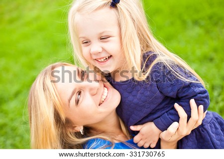 Young beautiful blonde mother and her cute little daughter smiling and relaxing in park in summer. Both wear blue dresses and laugh happily. Concept of happiness in parenthood and family - stock photo