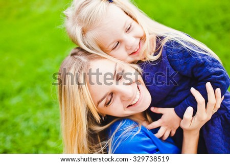 Young beautiful blonde mother close eyes and hug her little daughter smiling and relaxing in park in summer. Both wear blue dresses and laugh happily. Concept of happiness in parenthood and family - stock photo