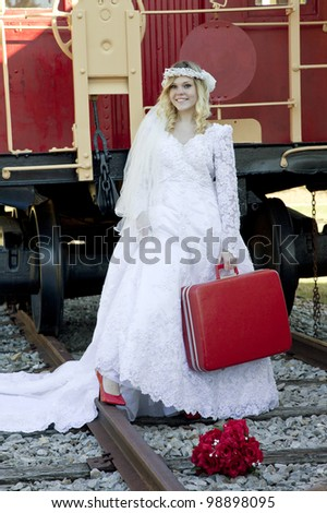 Young beautiful blonde runaway bride wearing red heels carrying red suitcase on train tracks behind old red and yellow caboose - stock photo