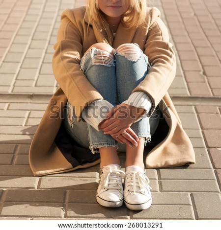 Young beautiful blonde sitting on the ground in summer sunny evening - stock photo
