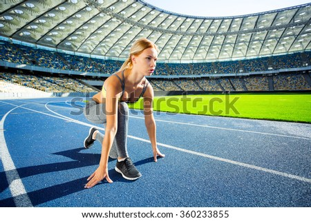 Young beautiful blonde sportswoman is ready to run on racetrack outdoors. Fit woman is at large nice modern stadium - stock photo