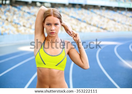 Young beautiful blonde sportswoman stretching on racetrack outdoors. Fit woman is at large nice modern stadium - stock photo