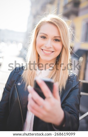 young beautiful blonde straight hair woman in the city using smartphone