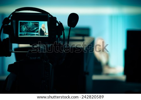Young beautiful blonde television announcer at studio during live broadcasting.Female TV director at editor in studio.Recording at TV studio with television anchorwoman. TV NEWS studio with camera - stock photo