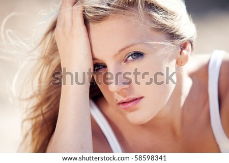 young beautiful blonde with developing on a wind hair