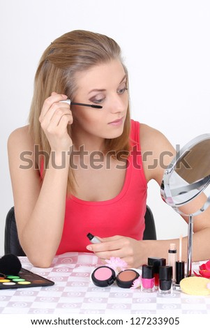 young beautiful blonde with make up accessories and mirror