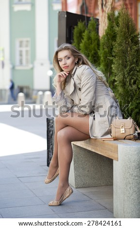 Young beautiful blonde woman in a beige coat sitting on a bench in the street - stock photo
